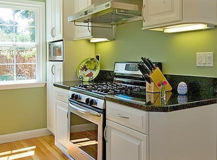 Темная столешница для кухни из ДСП в сочетании с зеленым фартуком